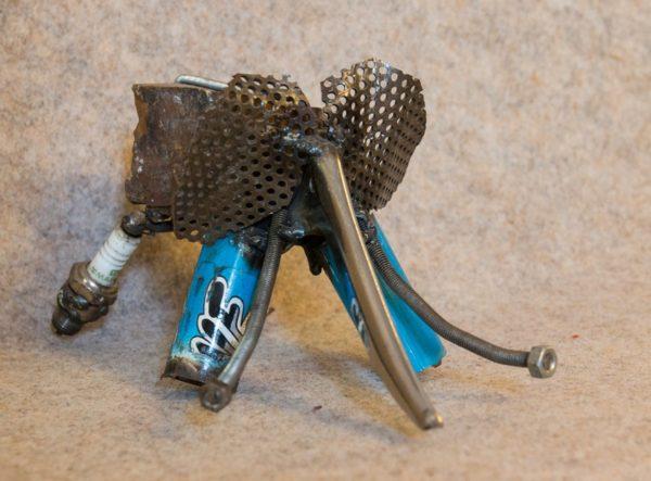 Petit éléphant en métal rouillé, de couleur bleue. Vue de face