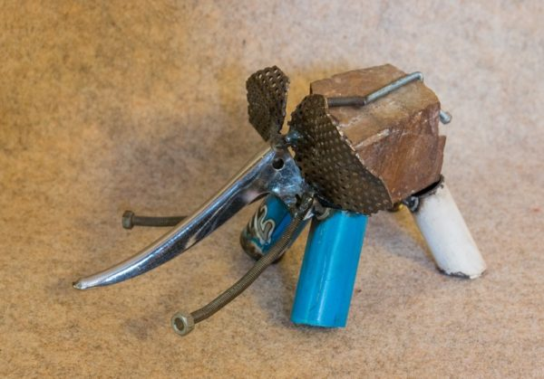 Petit éléphant en métal rouillé, de couleur bleue. Vue de profil droit