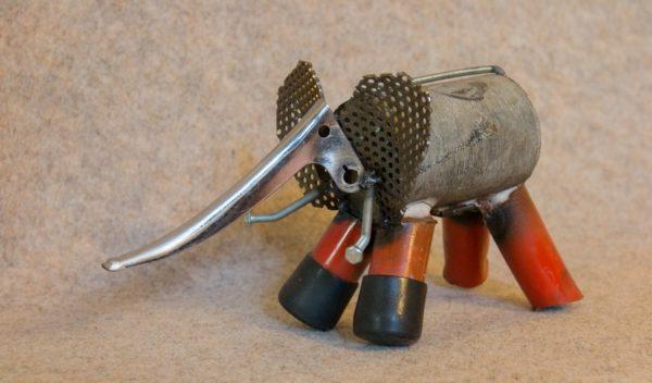 Un éléphant en métal aux pattes rouges, de profil